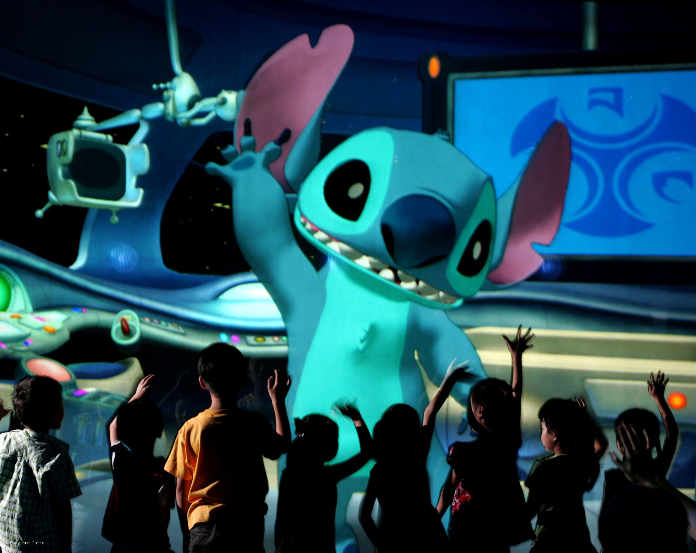 """0620AU_0369JD.jpg 0620AU_0383JD.jpg SAY HELLO TO 'STITCH': In this photo taken inside """"Stitch Encounter,"""" the tiny and talkative alien known as """"Stitch"""" waves to guests as they enter Space Control Traffic Center at Hong Kong Disneyland.  The mischievous blue alien, who debuted in Disney's hit animated comedy """"Lilo & Stitch,"""" stars in the new cutting-edge attraction where park guests, seated in an intimate theatre, carry on real-time conversations with the famous animated character.  The jaw-dropping technology allows for Disney fun like never before.  Stitch, aka """"Experiment 626,"""" can talk to guests, play games and interact with them in surprising new ways.  When it officially opens to guests July 13, 2006, Stitch Encounter will be presented daily in three languages – Cantonese, English and Putonghua.  Hong Kong Disneyland is the first and only Disney theme park in the world where guests can experience Stitch Encounter. (Jimmy DeFlippo, photographer)"""